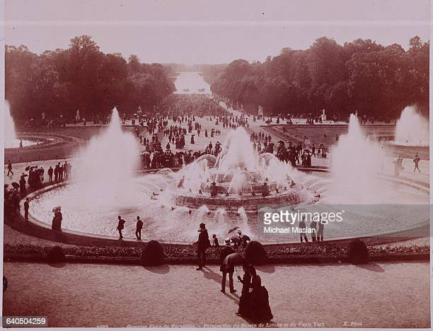 Pedestrians stroll by a grand fountain known as the Bassin de Latone in the Gardens of Versailles France ca 1880s1890s