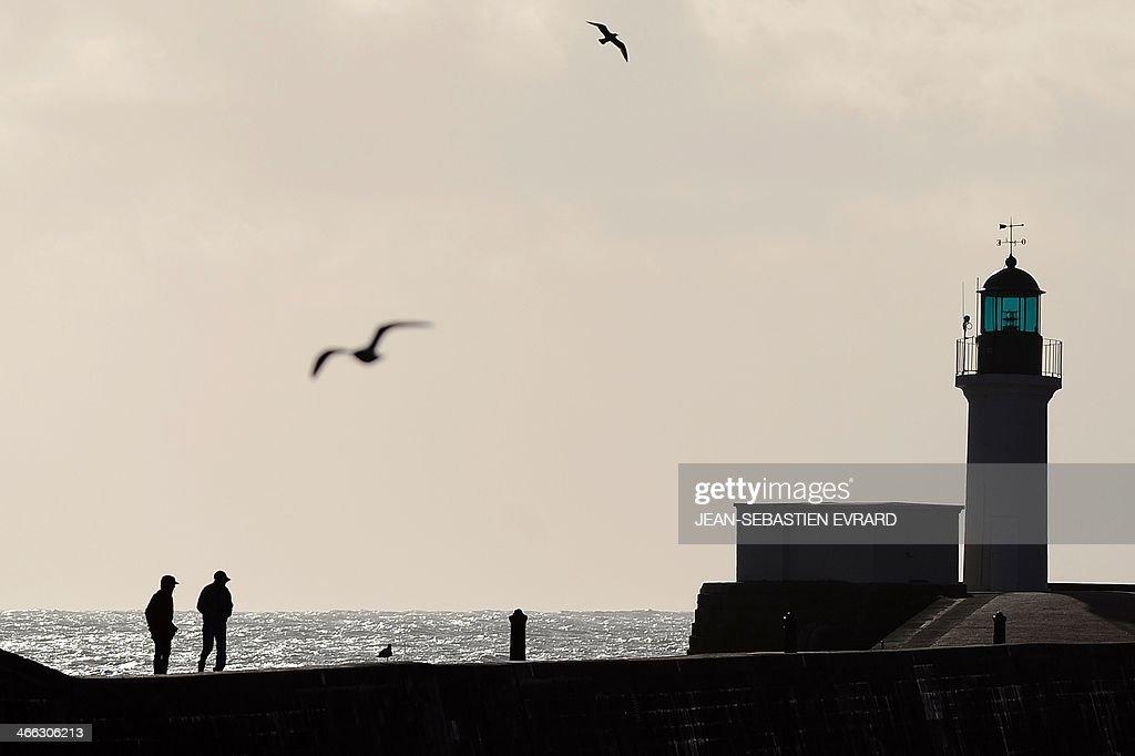 Pedestrians stroll on a pier by a lighthouse on the Atlantic ocean coastline on February 1, 2014 in Les Sables-d'Olonne, western France. AFP PHOTO / JEAN-SEBASTIEN EVRARD