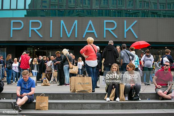 Pedestrians take a break from shopping outside a Primark store in Berlin Germany on Saturday May 23 2015 German investment and consumption rose last...