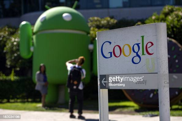 Pedestrians take photographs in front of a Google Inc office building at the company's headquarters in Mountain View California US on Friday Sept 27...