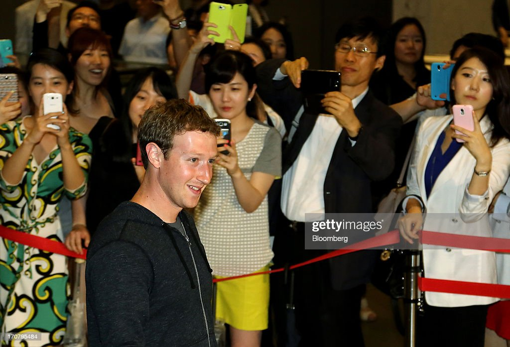 Pedestrians take photographs of <a gi-track='captionPersonalityLinkClicked' href=/galleries/search?phrase=Mark+Zuckerberg&family=editorial&specificpeople=4841191 ng-click='$event.stopPropagation()'>Mark Zuckerberg</a>, chief executive officer of Facebook Inc., as he leaves Samsung Electronic Co.'s Seocho office building in Seoul, South Korea, on Tuesday, June 18, 2013. Zuckerberg met Park Geun Hye, South Korea's president, in Seoul earlier today and discussed ways to realize Park's vision to foster a 'creative economy' and boost tech start-ups in Korea, Park's office said in a statement on its website. Photographer: SeongJoon Cho/Bloomberg via Getty Images