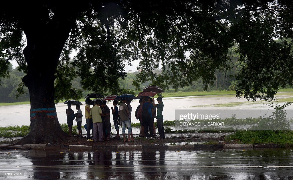 Pedestrians take shelter under a tree with their umbrellas during a rain shower in Kolkata on August 19, 2013.The monsoon season, which runs from June to September, accounts for about 80 percent of India's annual rainfall, vital for a farm economy which lacks adequate irrigation facilities. However, the flooding also causes hundreds of deaths and damage to infrastructure, homes and farms across India. AFP PHOTO/Dibyangshu SARKAR