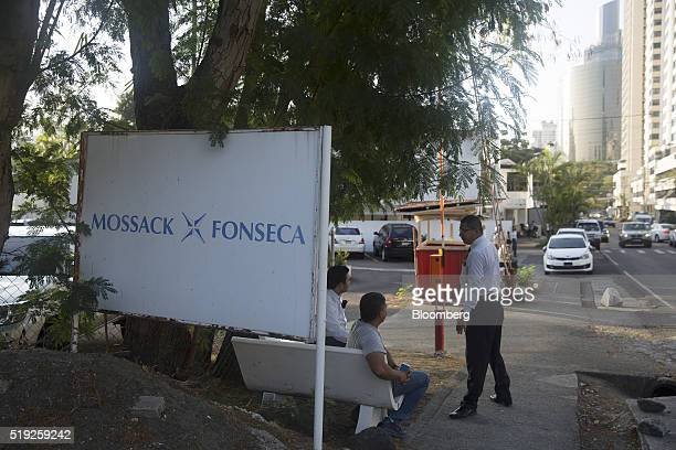 Pedestrians talk near a parking lot outside the building housing the offices of the Mossack Fonseca law firm in Panama City Panama on Tuesday April 5...