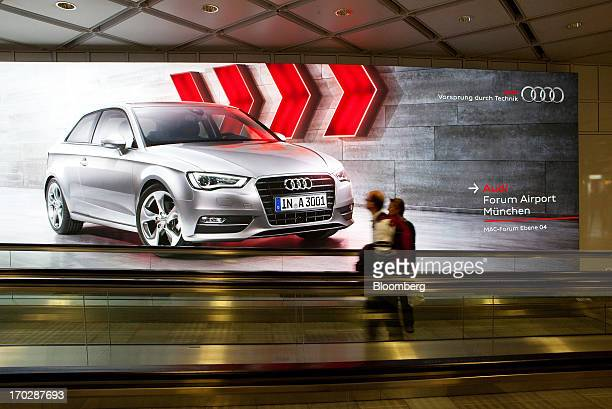 Pedestrians travel along a moving walkway at Munich airport and past a poster for an Audi AG event in Munich Germany on Sunday June 9 2013 German...
