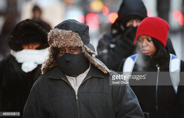 Pedestrians try to keep warm as they walk through downtown as the temperature hovered around 5 degrees January 27 2014 in Chicago Illinois The city...