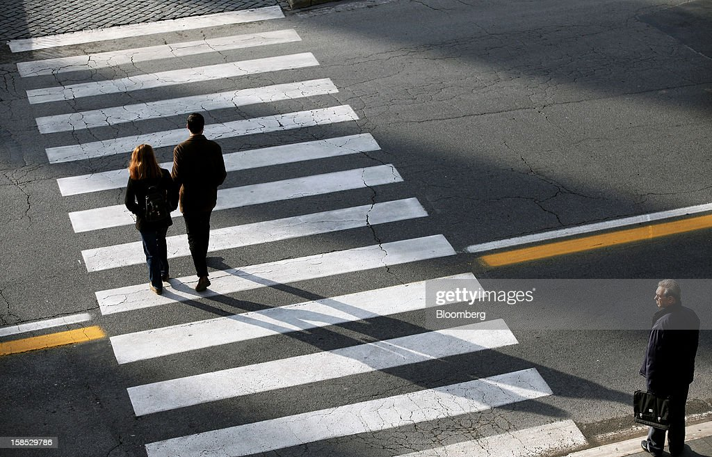 Pedestrians use a pedestrian crossing on a road in Rome, Italy, on Tuesday, Dec. 18, 2012. Italian Prime Minister Mario Monti, who is under pressure from euro-area and business leaders to enter the Italian election campaign, plans to quit once parliament passes his budget this week. Photographer: Alessia Pierdomenico/Bloomberg via Getty Images