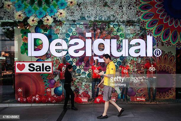 Pedestrians use mobile devices as they walk past sale signs in a Desigual SL store on Orchard Road in Singapore on Sunday June 21 2015 Consumer...