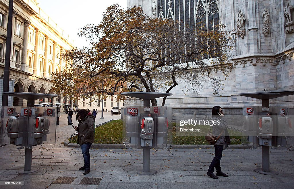Pedestrians use mobile phones as they stand near public payphones operated by Telecom Italia SpA, in Milan, Italy, on Tuesday, Nov. 20, 2012. Telecom Italia SpA said it is still reviewing the possible spinoff of its fixed-line network and the company's board will discuss the outcome of its analysis on Dec. 6. Photographer: Alessia Pierdomenico/Bloomberg via Getty Images