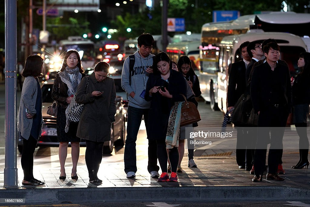 Pedestrians use mobile phones as they wait to cross a street at night in Gwanghwamun Square in Seoul, South Korea, on Tuesday, Oct. 22, 2013. Samsung Electronics is scheduled to release third-quarter earnings on Oct. 25. Photographer: SeongJoon Cho/Bloomberg via Getty Images