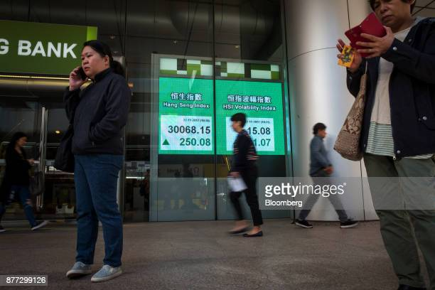 Pedestrians use smart phones near an electronic screen displaying the Hang Seng Index left and the HSI Volatility Index in Hong Kong China on...