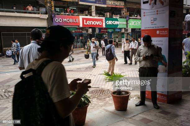 Pedestrians use smartphones at the Nehru Place IT Market in New Delhi India on Tuesday May 30 2017 Reliance Communications Ltd's credit rating...