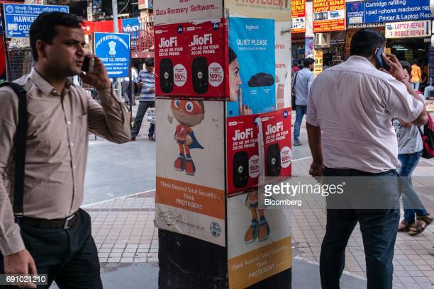 Pedestrians use smartphones near advertising for Reliance Jio Infocomm Ltd at the Nehru Place IT Market in New Delhi India on Tuesday May 30 2017...