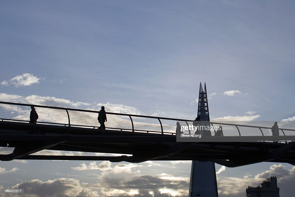 Pedestrians use the Millennium Bridge to cross the River Thames at dawn beyond the Shard tower in London, U.K., on Thursday, Jan. 31, 2013. The Shard, which stands at 309.6 meters on London's South Bank, opens to the public on Feb. 1, and is owned by LBQ Ltd., which brings together the State of Qatar (the majority shareholder) and Sellar Property Group Ltd., with non-equity funding by Qatar National Bank. Photographer: Simon Dawson/Bloomberg via Getty Images