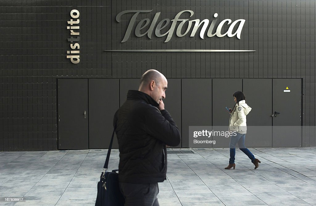 Pedestrians use their mobile phones as they pass a Telefonica logo outside the headquarters of Telefonica SA in Madrid, Spain, on Tuesday, April 30, 2013. Telefonica SA, Spain's largest phone company, is considering sale options in Europe that range from fixed-line operations in Germany to its assets in Ireland, according to people familiar with the plans. Photographer: Angel Navarrete/Bloomberg via Getty Images