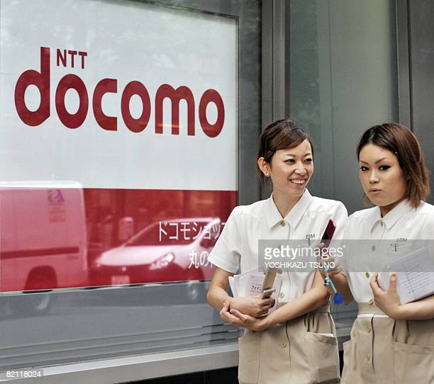 Pedestrians use their mobile phones as they walk past a NTT docomo shop in Tokyo on July 30 2008 Japan's top mobile operator NTT docomo said its net...