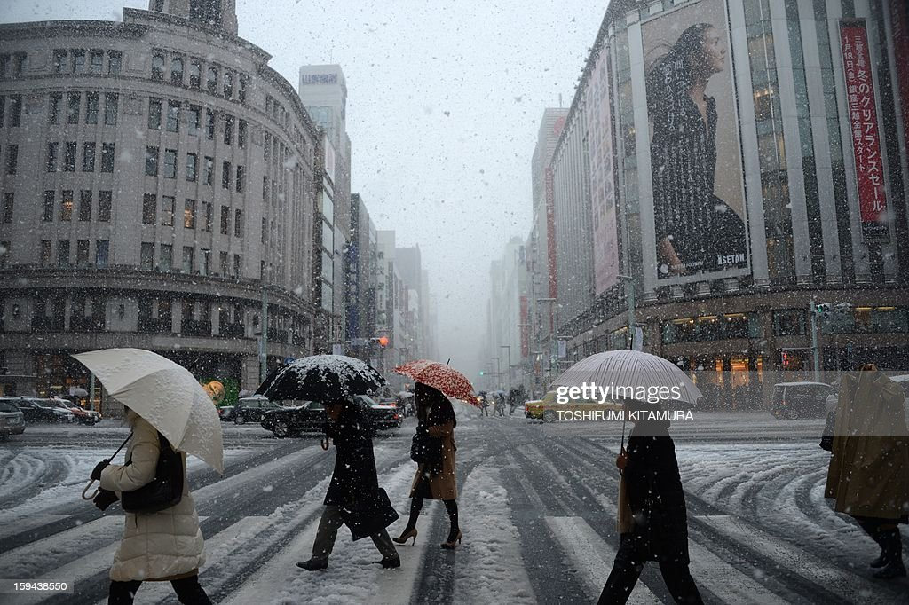 Pedestrians use their umbrellas to shelter from the falling snow as they cross the street in the Ginza shopping district in Tokyo on January 14, 2013. A storm system grasped central Japan on January 14, causing heavy snow fall around the Japanese capital.