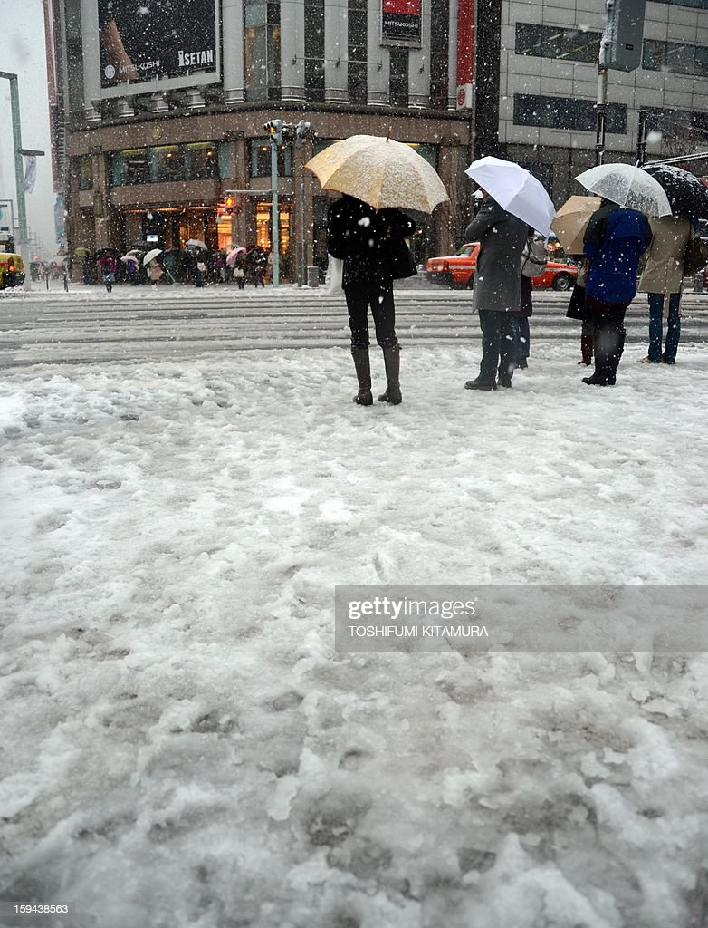 Pedestrians use their umbrellas to shelter from the falling snow as they wait for a signal to change to cross the street in the Ginza shopping district in Tokyo on January 14, 2013. A storm system grasped central Japan on January 14, causing heavy snow fall around the Japanese capital.
