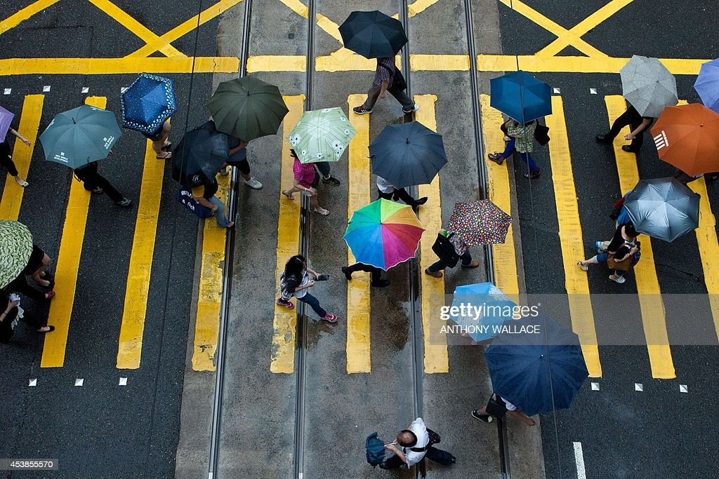 Pedestrians use umbrellas as they walk in the district of Central in Hong Kong on August 20, 2014. Hong Kong was handed back to China by Britain on July 1, 1997 under a 'one country, two systems' agreement, which allows residents civil liberties not seen on the mainland, including free speech and the right to protest. But public discontent is at its highest for years notably over Beijing's insistence that it vet candidates before the vote for the city's next leader in 2017.