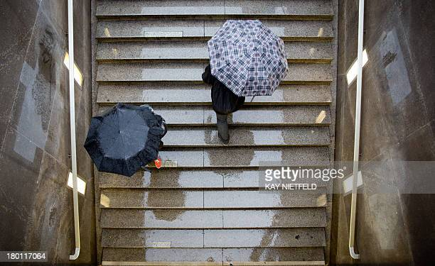 Pedestrians use umbrellas to shelter from the rain as they take stairs at Potsdamer Platz square on September 9 2013 in Berlin Temperatures in the...