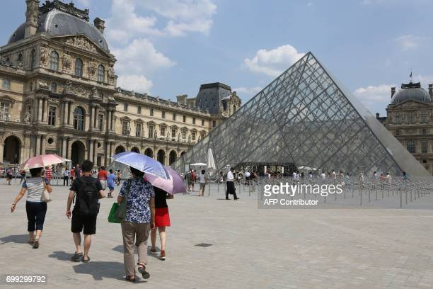 Pedestrians use umbrellas to shield themselves from the sun near The Louvre Museum in Paris on June 21 as temperatures climb across Europe Europe...
