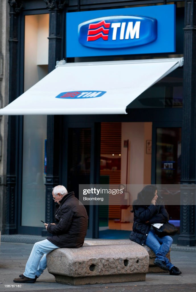 Pedestrians uses mobile phones as they sit outside a TIM store, the mobile unit of Telecom Italia SpA, in Milan, Italy, on Tuesday, Nov. 20, 2012. Telecom Italia SpA said it is still reviewing the possible spinoff of its fixed-line network and the company's board will discuss the outcome of its analysis on Dec. 6. Photographer: Alessia Pierdomenico/Bloomberg via Getty Images