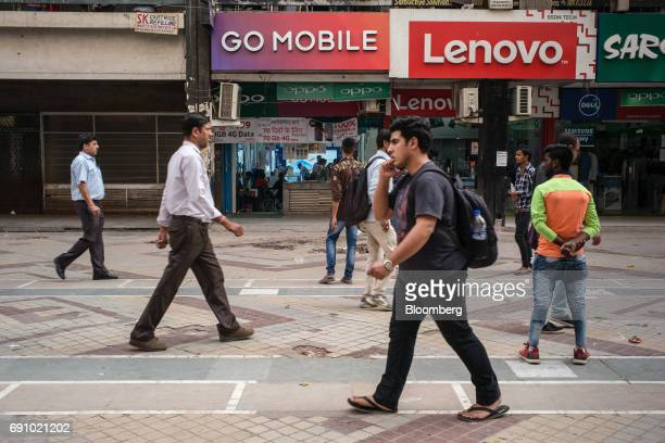 A pedestrians using a smartphones walks past stores selling mobile phones and accessories at the Nehru Place IT Market in New Delhi India on Tuesday...