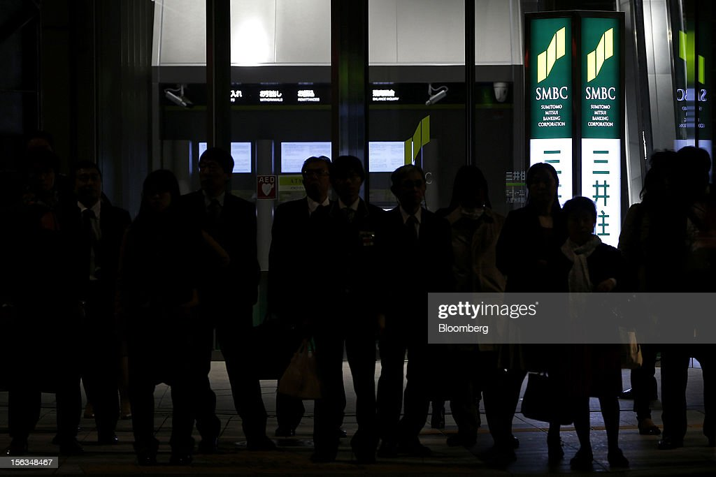 Pedestrians wait at a crossing outside a Sumitomo Mitsui Banking Corp. branch in Tokyo, Japan, on Tuesday, Nov. 13, 2012. Sumitomo Mitsui Financial Group Inc. is scheduled to announce first-half earnings results on Nov. 14. Photographer: Kiyoshi Ota/Bloomberg via Getty Images