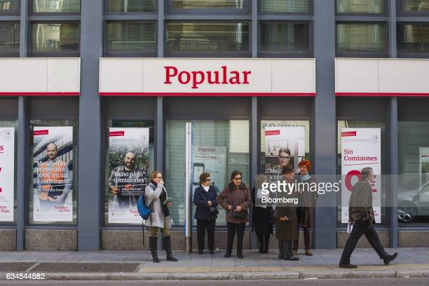 Pedestrians wait for a bus in front of a Banco Popular Espanol SA bank branch in Madrid Spain on Friday Feb 10 2017 Banco Populars new Chairman...