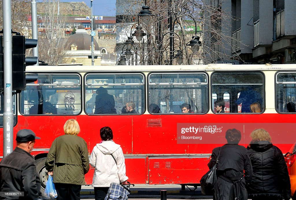 Pedestrians wait for a bus to pass before crossing a street in central Skopje, Macedonia, on Sunday, March 17, 2013. Macedonia's economy contracted by a real 0.3% on the year in 2012, compared to a growth of 2.8% a year earlier, an estimate released by the country's statistics office showed. Photographer: Oliver Bunic/Bloomberg via Getty Images