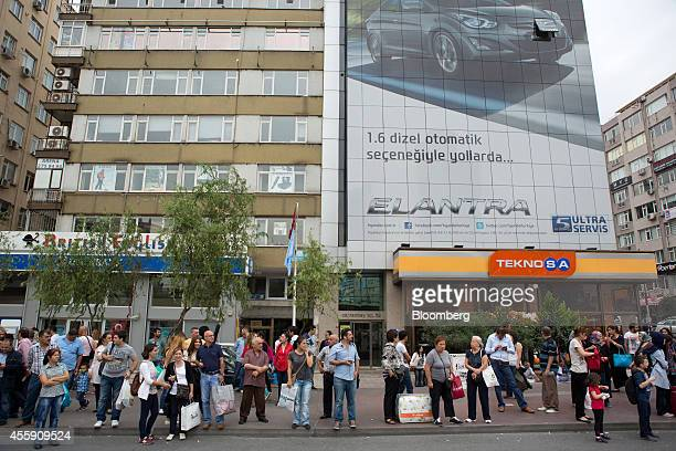 Pedestrians wait for public buses at a roadside beneath a billboard advertising the Hyundai Motor Co Elantra automobile in the Mecidiyekoy district...
