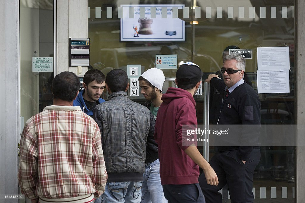 Pedestrians wait outside a Bank of Cyprus Plc branch as banks open for the first time in two weeks in Nicosia, Cyprus, on Thursday, March 28, 2013. The Central Bank of Cyprus's capital controls will include a 300-euro ($383) daily limit on withdrawals and restrictions on transfers to accounts outside the country. Photographer: Simon Dawson/Bloomberg via Getty Images