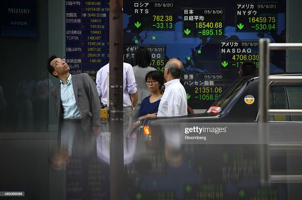 Pedestrians wait to cross a road in front of an electronic stock board outside a securities firm in Tokyo Japan on Monday Aug 24 2015 Japanese stocks...