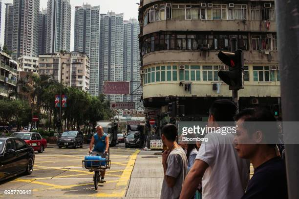 Pedestrians wait to cross a road in the Sham Shui Po district of Hong Kong China on Saturday April 29 2017 Hong Kong a city of soaring skyscrapers...