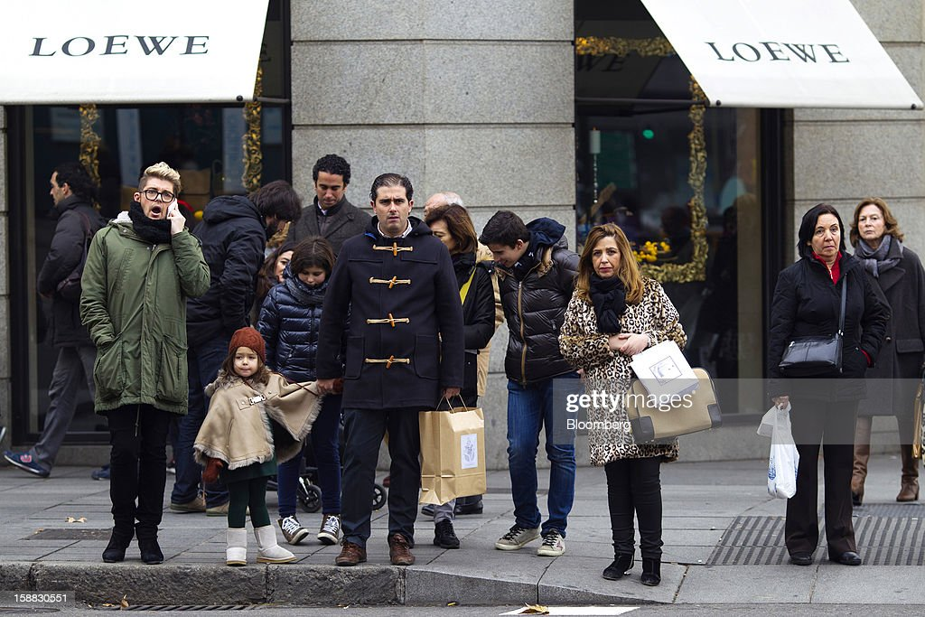 Pedestrians wait to cross a street outside a Loewe AG luxury store in central Madrid, Spain, on Saturday, Dec. 29, 2012. Spain's economic activity kept falling in the fourth quarter, Bank of Spain says. Photographer: Angel Navarrete/Bloomberg via Getty Images