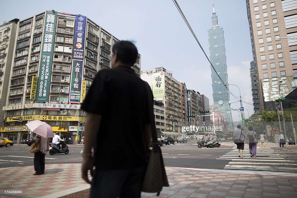 Pedestrians wait to cross the street at an intersection on Hsin Yi Road as the Taipei 101 building stands in the background in Taipei, Taiwan, on Wednesday, July 24, 2013. Taiwan President Ma Ying-jeou ruled out driving down the Taiwan dollar to boost exports following the currencys rally against the yen and said the government still aims for growth of at least 2 percent this year. Photographer: Jerome Favre/Bloomberg via Getty Images