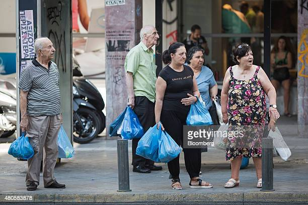 Pedestrians wait with their shopping bags at a bus stop near Varvakeios fish and meat market in Athens Greece on Monday July 13 2015 Greece has been...