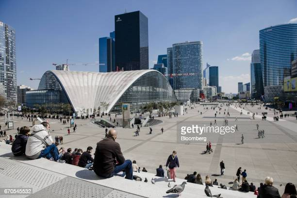 Pedestrians walk across a plaza while people sit on steps as skyscrapers including the headquarters of Areva SA center stand in La Defense business...