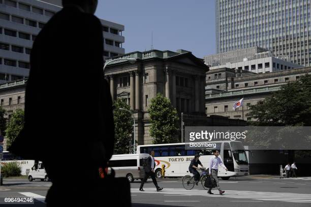 Pedestrians walk across the street in front of the Bank of Japan headquarters in Tokyo Japan on Friday June 16 2017 Global stocks rose with shares in...