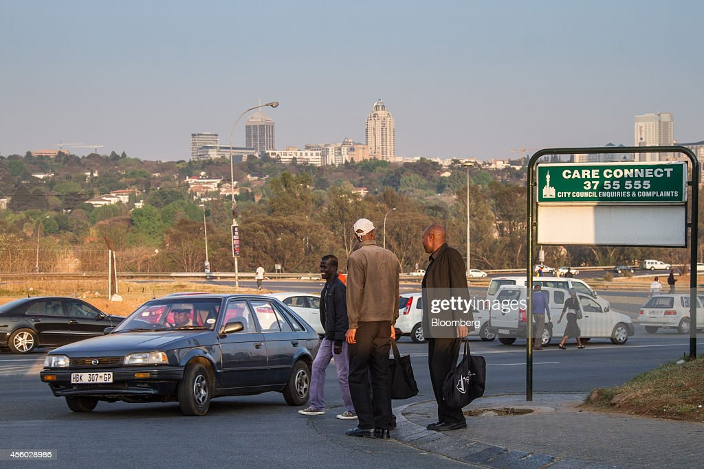 Pedestrians walk along a highway from Alexandra township towards Sandton in Johannesburg South Africa on Tuesday Sept 23 2014 Sandton once a single...
