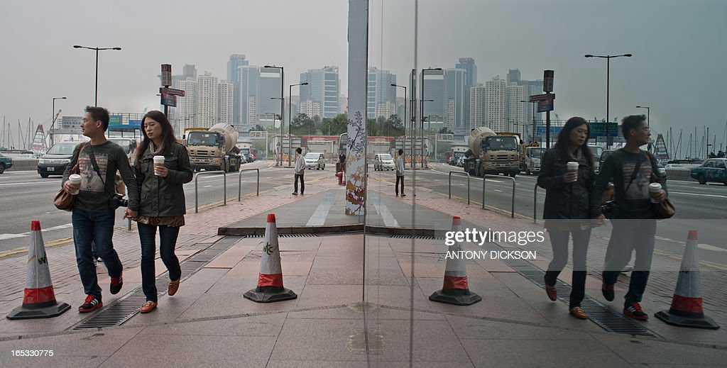 Pedestrians walk along a road as they are reflected in a building's facade in Hong Kong on April 3, 2013. The southern Chinese financial hub saw growth of 1.4 percent in 2012 and was tipped to expand only 1.5-3.5 percent this year. AFP PHOTO / Antony DICKSON