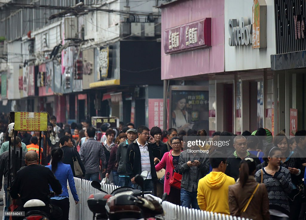 Pedestrians walk along a shopping street in Wuhan, China, on Thursday, Oct. 17, 2013. China is scheduled to release third-quarter gross domestic product figures on Oct. 18. Photographer: Tomohiro Ohsumi/Bloomberg via Getty Images