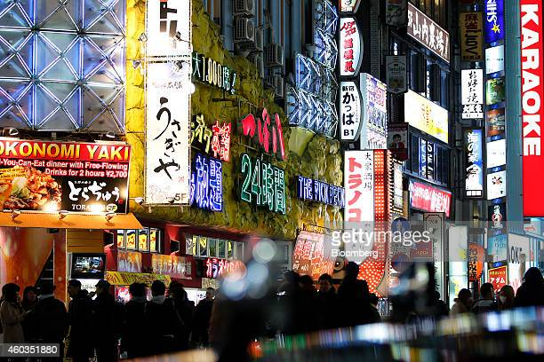 Pedestrians walk along a street illuminated with neon signs in Tokyo Japan on Thursday Dec 11 2014 Japanese stocks rose ahead of national elections...