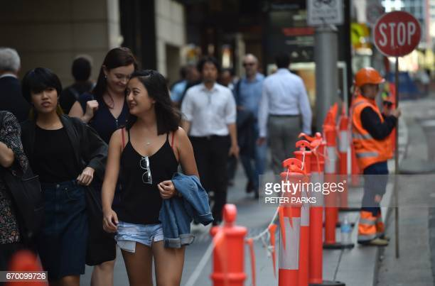 Pedestrians walk along a street in the central business district of Sydney on April 19 2017 Australia's controversial decision to scrap a visa...