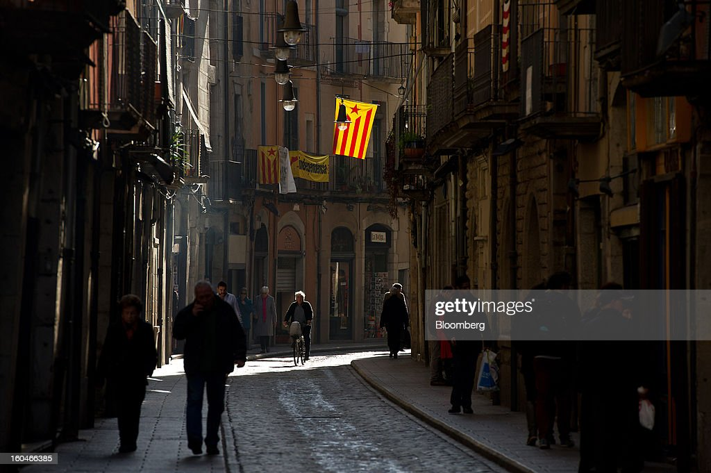 Pedestrians walk along a street while a cyclist passes beneath a pro-independence Catalan flag hanging from a residential building in Girona, Spain, on Thursday, Jan. 31, 2013. Spain's recession deepened more than economists forecast in the fourth quarter as the government's struggle to rein in the euro region's second-largest budget deficit weighed on domestic demand. Photographer: David Ramos/Bloomberg