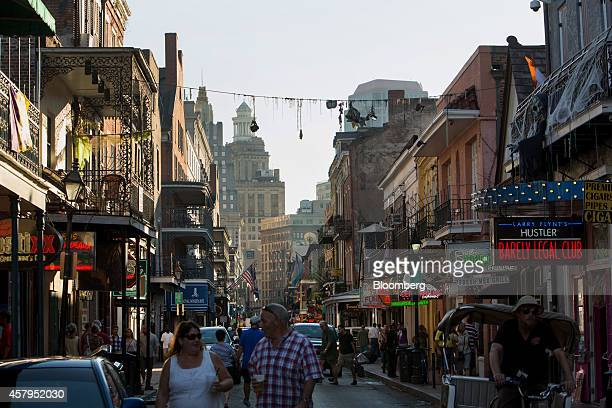 Pedestrians walk along Bourbon Street in the French Quarter neighborhood of New Orleans Louisiana US on Tuesday Oct 21 2014 New Orleans one of the...