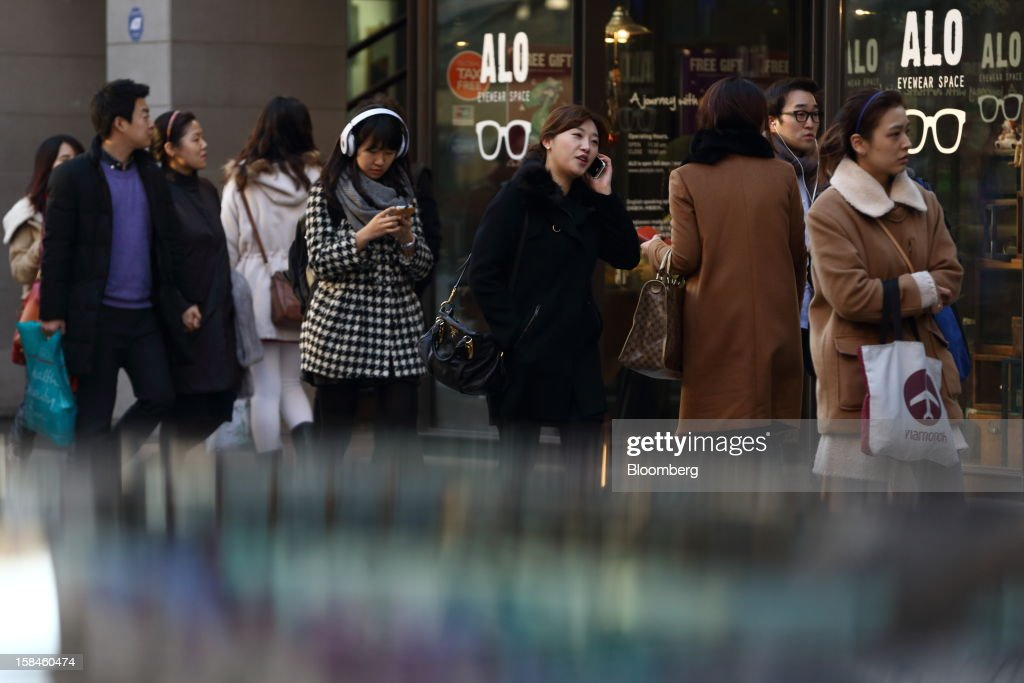 Pedestrians walk along Garosugil street in the Gangnam district of Seoul, South Korea, on Saturday, Dec. 15, 2012. South Koreans vote on Dec. 19 to replace President Lee Myung Bak, whose five-year term ends in February. Photographer: SeongJoon Cho/Bloomberg via Getty Images