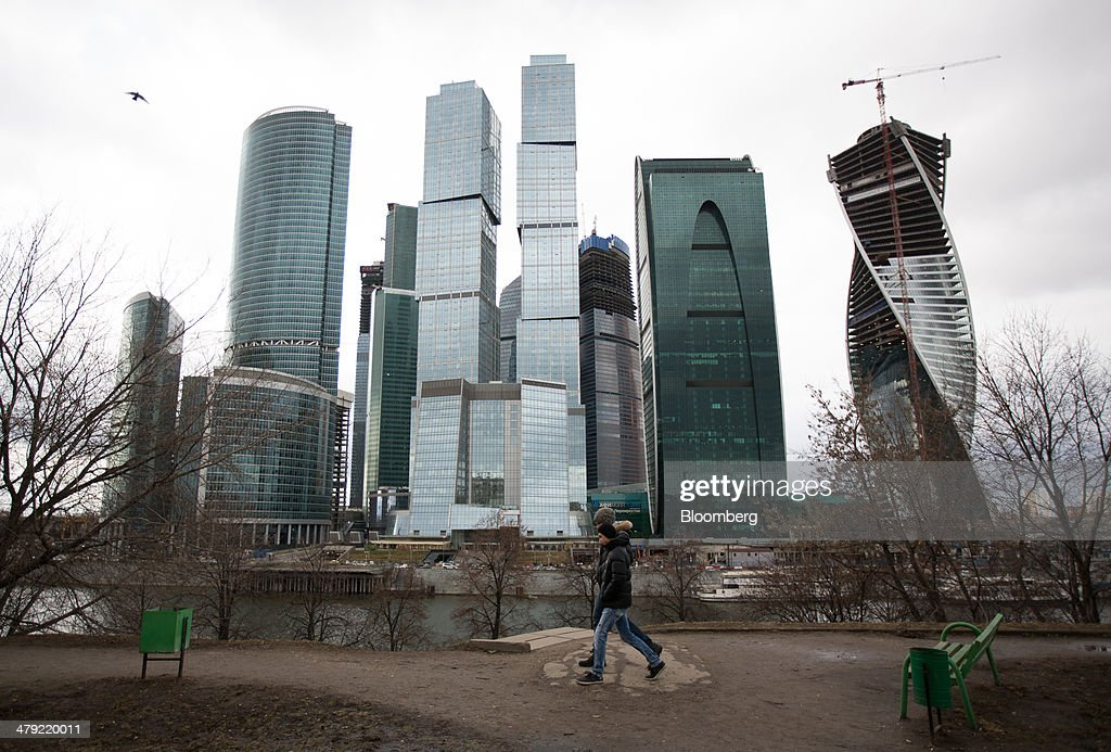 Pedestrians walk along the banks of the Moskva river opposite the Moscow International Business Center, also known as 'Moscow City,' in Moscow, Russia, on Sunday, March 16, 2014. The U.S. and the European Union warned Russia not to annex Crimea after a referendum in the southern Ukrainian region, setting the stage for sanctions on Russia in the worst diplomatic standoff since the Cold War. Photographer: Andrey Rudakov/Bloomberg via Getty Images