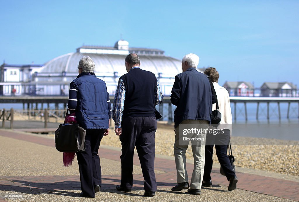 Pedestrians walk along the beachfront promenade near Eastbourne Pier in Eastbourne, U.K., on Tuesday, April 1, 2014. Pensioners and savers have seen returns on their money shrink since the financial crisis drove interest rates to a record low. Photographer: Chris Ratcliffe/Bloomberg via Getty Images