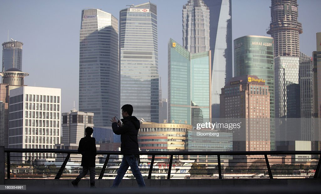Pedestrians walk along the Bund as commercial buildings stand in the Pudong area in Shanghai, China, on Monday, Jan. 28, 2013. China's economic growth accelerated for the first time in two years as government efforts to revive demand drove a rebound in industrial output, retail sales and the housing market. Photographer: Tomohiro Ohsumi/Bloomberg via Getty Images