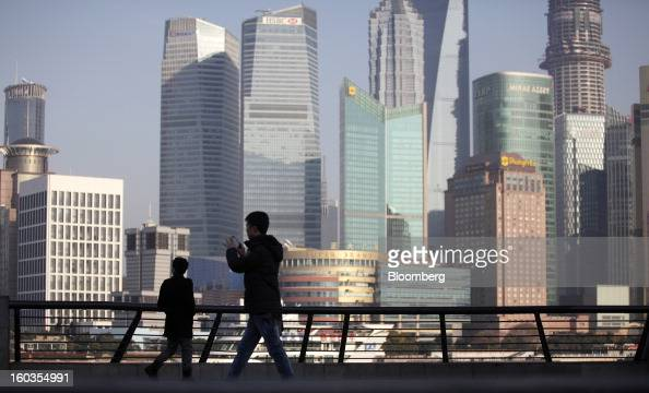 Pedestrians walk along the Bund as commercial buildings stand in the Pudong area in Shanghai China on Monday Jan 28 2013 China's economic growth...